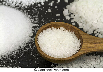 Rock Salt and thin salt with wooden spoon on black stone...