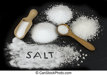 Various salt and wooden spoon on black stone background.