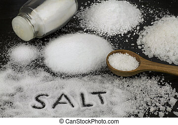 Salt and wooden spoon on black stone background.