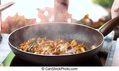 Mushrooms frying in slow motion. Chanterelles, rosemary and...