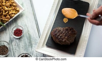 Steak and cognac sauce. Male hand with spoon. Cooking...