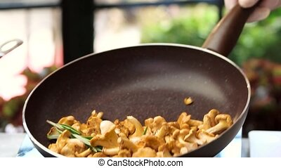 Flipping food in a pan. Chanterelles with garlic and...