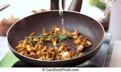 Water pouring in frying pan. Golden chanterelles and...