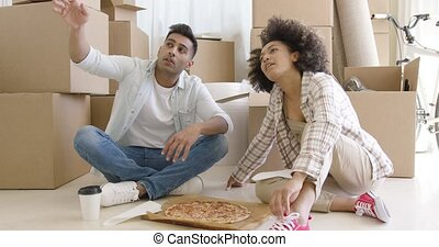 Young couple eating pizza and chatting