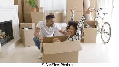 Happy mixed race couple having fun break with unpacking...