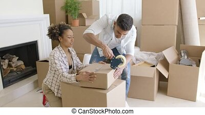 Young couple packing boxes to move home working as a team to...