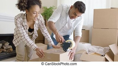 Couple taping boxes as they pack up their home - Young...