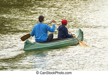 Family on canoe tour. Father and child paddling in kayak