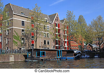 dutch buldings and houseboat along canal, Amsterdam -...