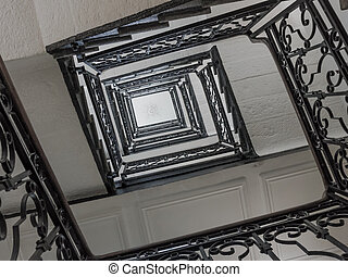 Upside view of a staircase. stair of antique square staircase stairwell of concrete and metal