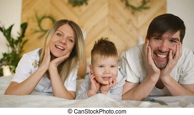 Portrait of a lovely family posing and smiling on bed in their bedroom