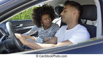 Young couple having a serious talk in a car with focus to...