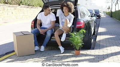 Young couple relaxing while moving house sitting in the open...
