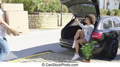 Cute young woman sitting in the trunk of a car as her...