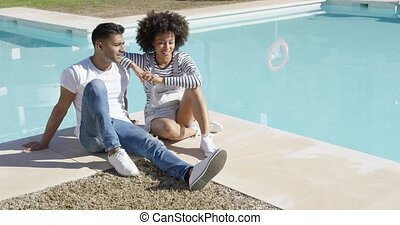 Young woman relaxing with her boyfriend poolside - Young...