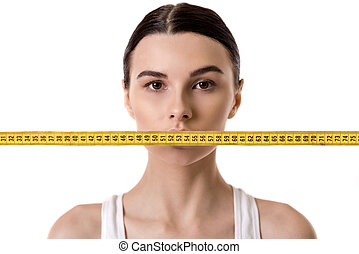 Girl and weight loss - Portrait of girl with a tape measure...