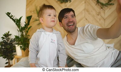 Young smiling father with son on bed taking selfie photo with smartphone camera