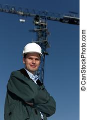 Engineer in hardhat against crane