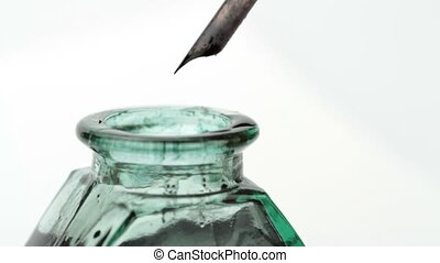 Hand writing with quill pen and old glass ink bottle