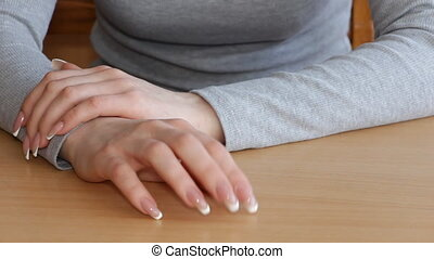 Young Woman taps her fingers on the table