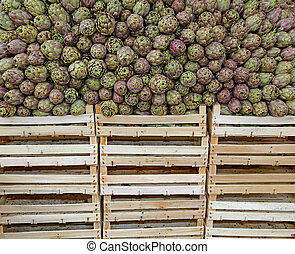 green artichokes and boxes for sale at the grocery store -...