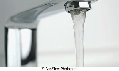 Stream of water pouring from chrome-plated faucet -...