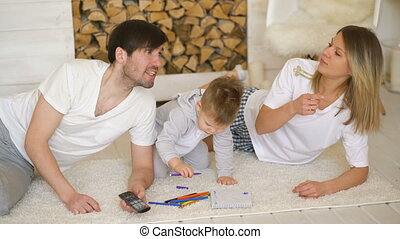 Father man mother watch TV while their son draw picture in their living room