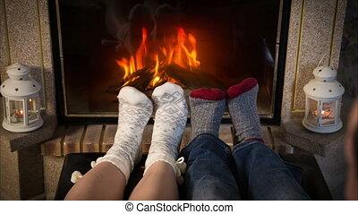 Legs of couple in woolen socks heat up near fireplace - Legs...