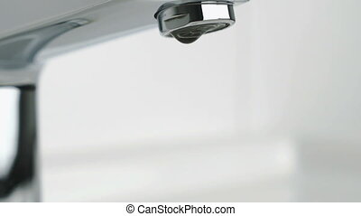 Water dripping from chrome-plated faucet. Close-up