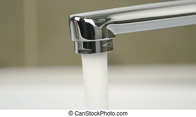 Strong flow of water pouring from chrome tap - Chrome-plated...