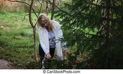 Young woman touching fir tree - Young blonde woman touching...