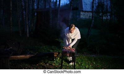 Fish cooking on grill at night