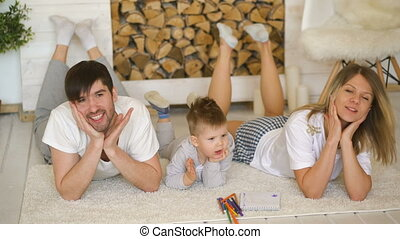 Portrait of a lovely family posing and smiling on floor in their living room