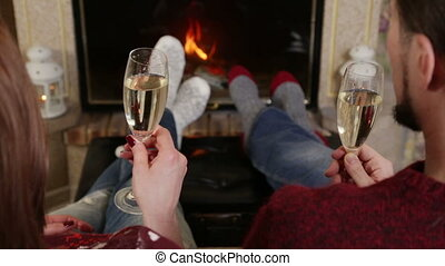 Couple toasting of champagne together near fireplace -...