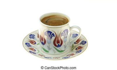 Drinking Turkish coffee with traditional ottomans motif cup...