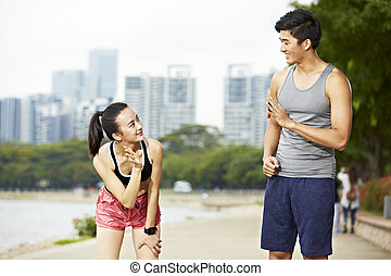 asian man and woman runner saying hello to each other