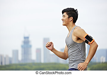 young asian man running in park - young asian male jogger...