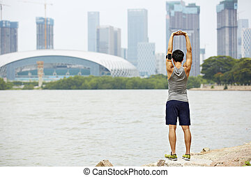 young asian jogger stretching arms before running - young...