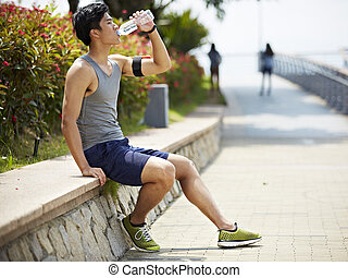 young asian jogger resting and drinking water - young...