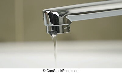 Weak flow of water pouring from chrome-plated tap -...