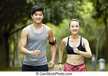 young asian couple running jogging in a park