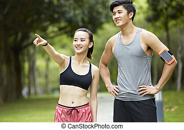 young asian couple exercising in city park