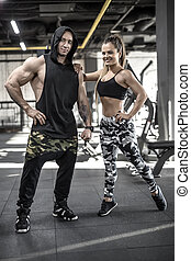 Sportive couple in gym - Smiling couple stand in the gym....