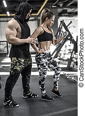 Athletic couple in gym - Sportive couple in the gym. Girl...