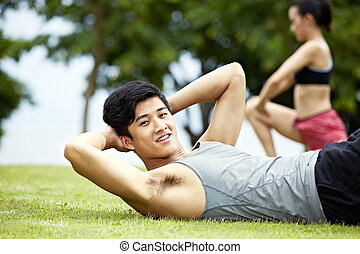 young man doing sit-ups in park