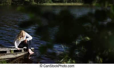 Young woman sitting near lake and touching water