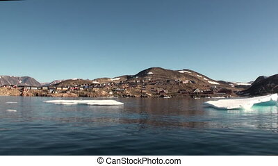 Settlement in the mountains on the shores of of Greenland Arctic Ocean.