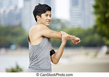 young asian man stretching arms