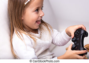 Excited little girl having fun playing video games holding...