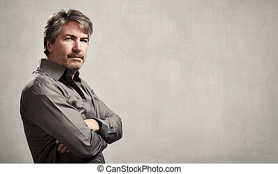 Man portrait - Mature handsome man portrait over gray wall...